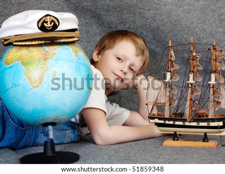 Portrait of the cute dreaming child with the model ship and globe - stock photo