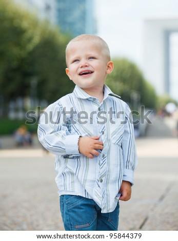 Portrait of the cute little boy walking to la Defense, Paris