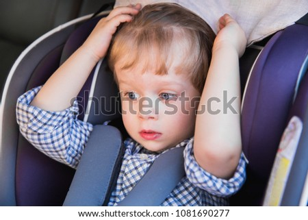 Portrait of the cute little boy who is sitting in the baby car seat in a car #1081690277