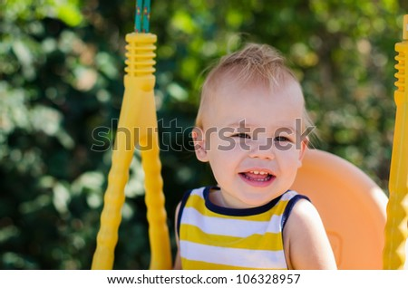 Portrait of the dear smiling child shaking on a swing