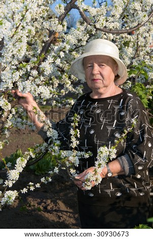 Portrait of the elderly woman on a background blossoming plums