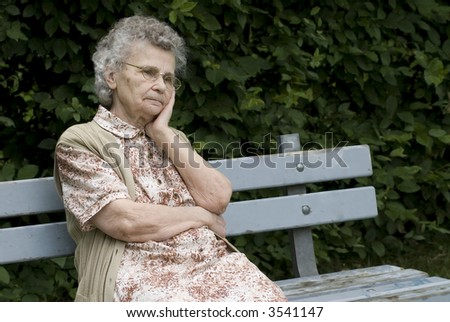 portrait of the elderly woman on the the park bench