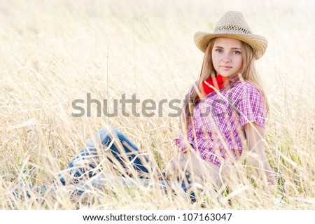 Portrait of the girl - cowboy in a grass