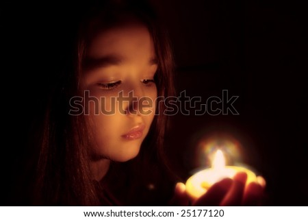 Portrait of the girl with a candle in hands. The spirituality face . Mood of sacrament and revelation.