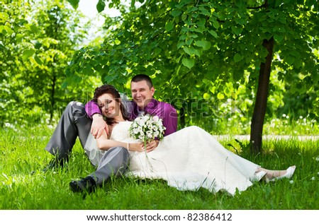 Portrait of the groom and the bride in park on a grass in the summer sunny day