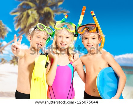 Portrait of the happy children enjoying at beach.  Schoolchild kids standing together in bright color swimwear with swimming mask on head .