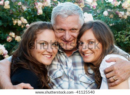 Portrait of the happy elderly father with two daughters - stock photo