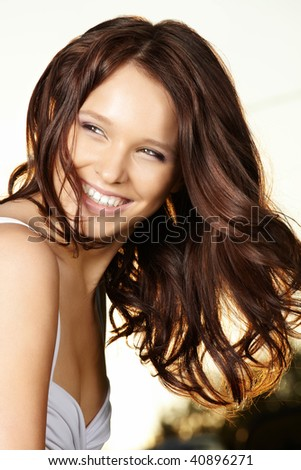 Portrait of the laughing curly beautiful woman in sunlight beams