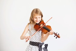 Portrait of the little violinist. Beautiful gifted little girl playing on violin against the white background