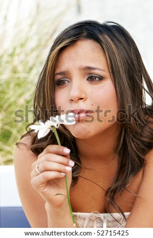 Portrait of the lonely crying girl with a flower