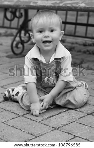 Portrait of the lovely funny laughing little boy playing outdoors