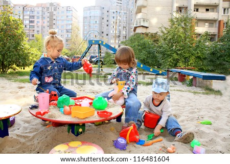 Portrait of the lovely little kids playing at the playground