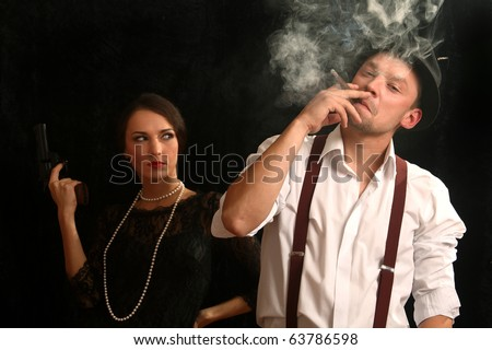 Portrait of the man in a hat with a pistol and the beautiful woman. In style of a retro.