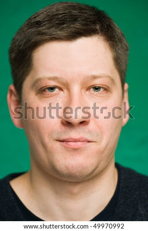 Portrait of the man on green background. Focus on eyes, small depth of field.
