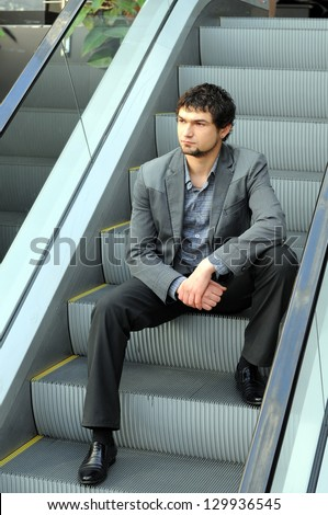 Portrait of the modern young man on the escalator
