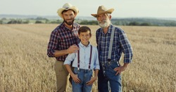 Portrait of the old farmer man standing in his field full of harvest together with his son and grandson.