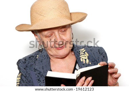 Portrait of the old woman in a hat with the book on a light background
