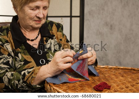 Portrait of the old woman with a needle and a thread