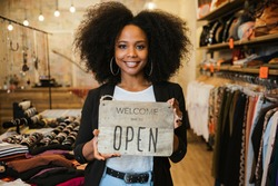 Portrait of the owner of the clothing store holding the sign with the words