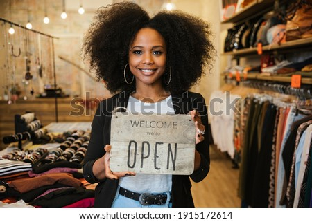 """Portrait of the owner of the clothing store holding the sign with the words """"Welcome we're open"""" in her hand to be attached to the window - Millennial woman welcomes customers at the entrance"""