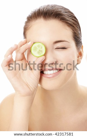 Portrait of the playful girl covering an eye by a slice of a cucumber, isolated
