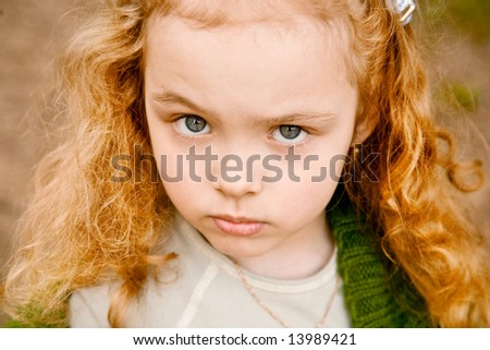 Portrait of the serious grey-eyed little girl with the long hair, looking in a shot