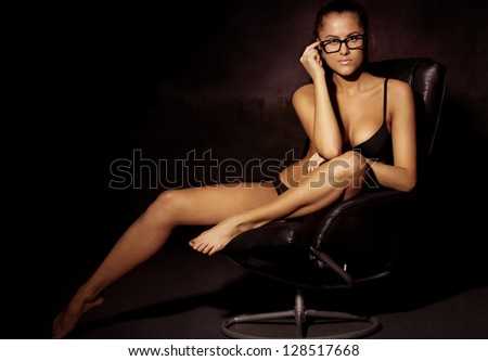 portrait of the sexy business woman in a bathing suit and wearing spectacles