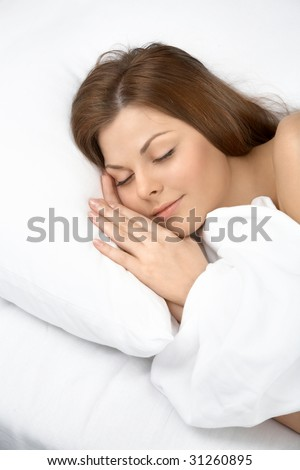 Portrait of the sleeping young woman in white bed