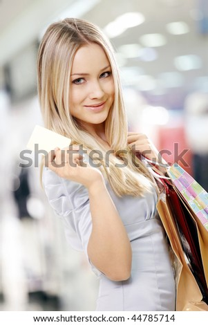 Portrait of the smiling blonde in shop with a credit card in a hand
