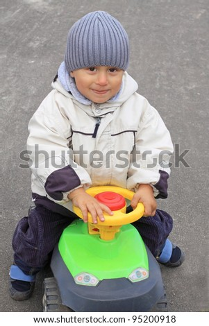 Portrait of the smiling boy driving the toy car