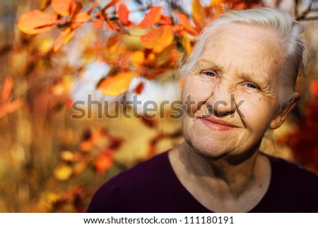 Portrait of the smiling elderly woman. A photo on the autumn background