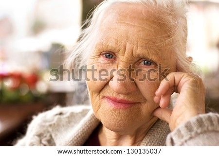 Portrait of the smiling elderly woman, sitting outdoor