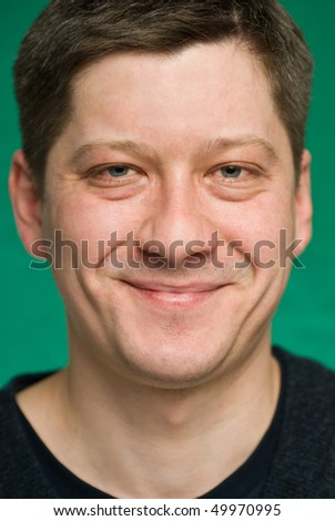 Portrait of the smiling man on green background. Focus on eyes, small depth of field.