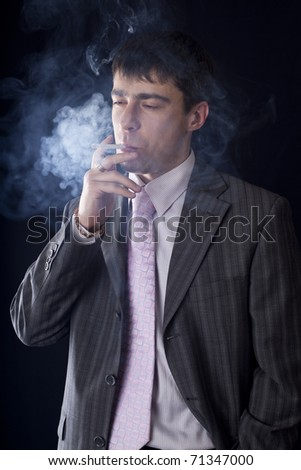 Portrait of the smoking man on a black background