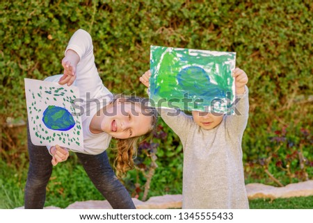 Portrait of the two cute little girls holding the drawing earth globe. Children draw a picture of earth having fun outdoor. GDPR, earth day, free plastic green world concept.