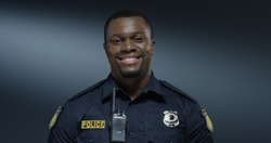 Portrait of the young African American good looking and cheerful policeman smiling to the camera. Close up.