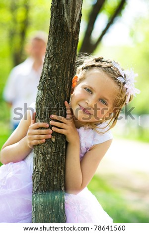Portrait of the young beautiful happy girl near the tree