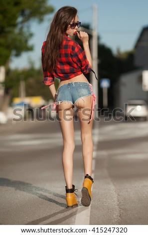 Stock Photo Portrait of the young beautiful smiling woman outdoors enjoying summer sun. Young woman outdoors portrait. Woman in jeans shorts and red shirt. Sexy woman buttocks.