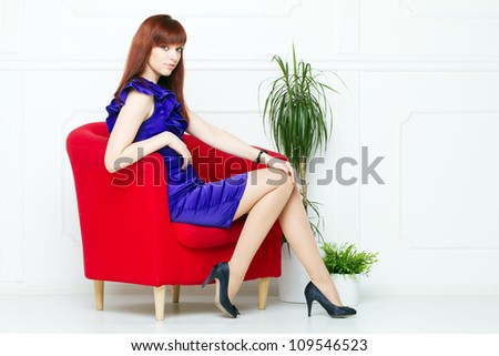 Portrait of the young beautiful woman in a red chair