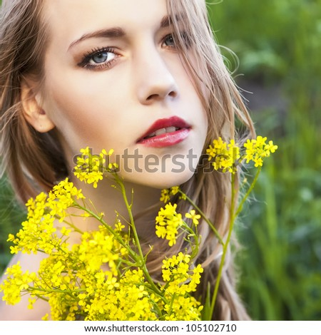 Portrait of the young beautiful woman with flowers