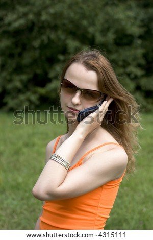 Portrait of the young girl in glasses speaking by phone