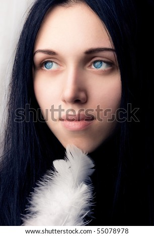 Portrait of the young girl with the beautiful blue eyes, a  holding a bird feather in a hand