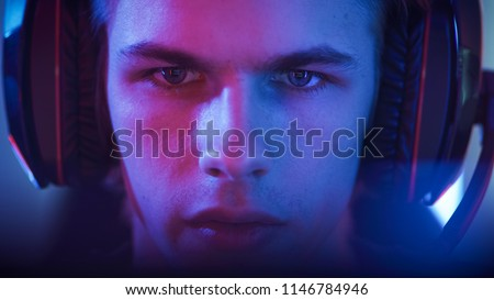 Portrait of the Young Handsome Pro Gamer Playing in Online Video Game. Neon Colored Room. e-Sport Cyber Games Internet Championship.