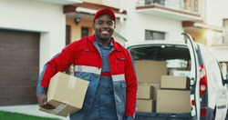 Portrait of the young smiled African American mailman with a box posing to the camera with carton box at the van. Outdoors.