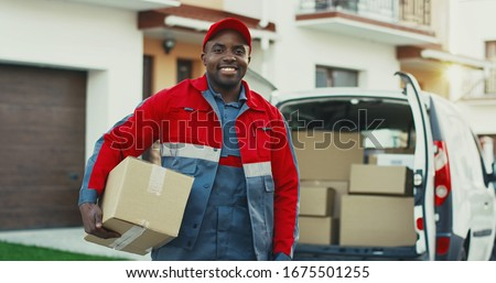 Portrait of the young smiled African American mailman with a box posing to the camera with carton box at the van. Outdoors. Stockfoto ©