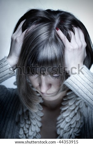 Portrait of the young woman with headache squeezing her head with hands, head down