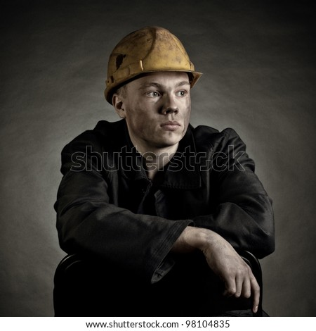Portrait of the young worker against a dark backgroun