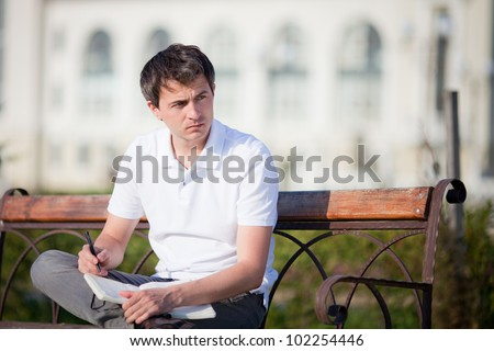 Portrait of thinking attractive man with notebook on a bench