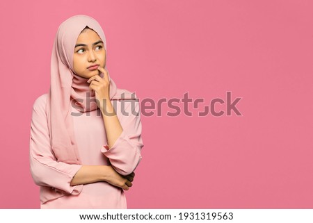 Portrait of thinking young Asian woman looking up and touch chin