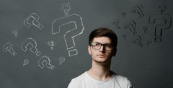 Portrait of thinkng young guy with question mark above his head.